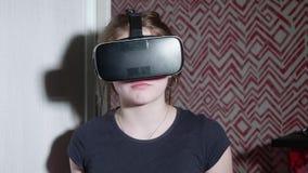 Asustan y se preocupa a la muchacha caucásica en vidrios de VR del suceso metrajes