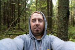 Asustaron a un hombre joven en un bosque grueso algo fotos de archivo
