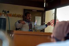 Egyptian artisan worker located at the door of a perfume factory in Aswan molding glass stock photo