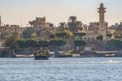 12.11.2018 Aswan, Egypt, a huge cruise ferry moving along a nile against the background of a city. On a sunny day royalty free stock photo