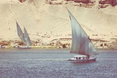 ASWAN, EGYPT - MARCH 25, 2017: Felucca river boat on the Nile,. With the Sahara behind in Aswan, Egipt Stock Photography