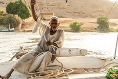 ASWAN, EGYPT 21.05.2018 Old Nubian Man Sitting on Felucca Boat Deck and Sailing Down the Nile River stock photography