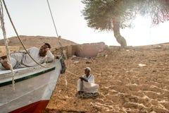 Aswan Egypte 21 05 18 Plaatselijke bevolking die op klanten tijdens van de de duinenkustlijn van het Zonsondergangzand de rivier  stock fotografie