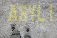 Asyl. Legs with gray boots and the word Asyl in german language on the ground. Concept for Refugees on their way to Germany royalty free stock photography