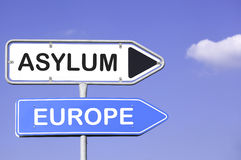 Asylum and Europe. Blue sky behind two white and blue road signs on a metal mast with arrows to the right side showing the way to Asylum and Europe. Social stock images
