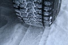 Tread area of winter tire packed with the snow close up. Asymmetrical winter tire with snow in tread blocks close upn Stock Image