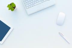 Asymmetrisk affärssammansättning på det vita kontorsskrivbordet med blomman royaltyfria bilder
