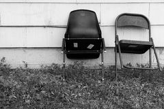 Asymmetry too. Chairs leaning up against a house in an asymmetrical composition. Black and white photo Royalty Free Stock Photos