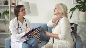 Asystent doktorska odwiedza stara kobieta z problemami w łączącym zdjęcie wideo