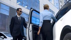 Asystent osobisty otwiera samochodowego drzwi jego szef żeński polityk, usługa obraz stock