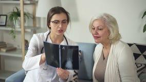Asystent patrzeje na promieniowaniu rentgenowskim z starszą kobietą doc zbiory wideo