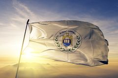Asyut Governorate of Egypt flag textile cloth fabric waving on the top sunrise mist fog. Beautiful stock photography