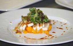 Atún asado a la parrilla con las zanahorias dulces hervidas y la ensalada cortada en trozos pequeños del arugula debajo de un vin Imagen de archivo libre de regalías