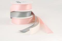 Atłasowe tasiemkowe rolki odizolowywać różowe szarość osrebrzają prezent Obraz Royalty Free