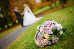 Atłasowy Bridal bukiet przed parą małżeńską niedawno Obraz Royalty Free