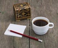Ataúd, café en una taza blanca y papel con un lápiz, un l inmóvil Foto de archivo