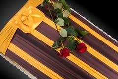 Ataúd cerrado con dos rosas rojas cubiertas con el paño elegante aislado en fondo gris primer del ata?d fotografía de archivo libre de regalías