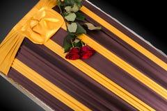 Ataúd cerrado con dos rosas rojas cubiertas con el paño elegante en fondo gris primer del ata?d imagenes de archivo