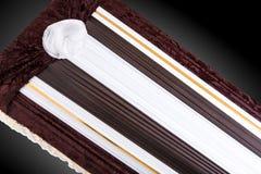 Ataúd cerrado cubierto con el paño elegante en fondo gris primer del ata?d imagen de archivo