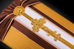Ataúd cerrado cubierto con el paño marrón y beige adornado con la cruz del oro de la iglesia en fondo de lujo gris Primer Fotografía de archivo