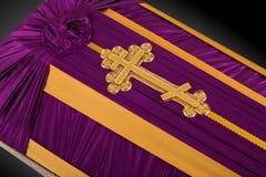 Ataúd cerrado cubierto con el paño púrpura y beige adornado con la cruz del oro de la iglesia en fondo de lujo gris Primer Imagen de archivo libre de regalías