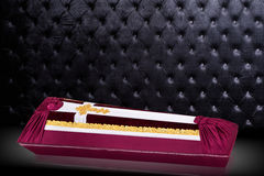 Ataúd cerrado cubierto con el paño rojo y blanco adornado con la cruz del oro de la iglesia en fondo de lujo gris Fotografía de archivo