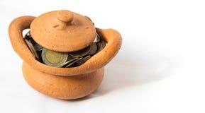 Ataúd de la arcilla por completo de las monedas para el concepto de la economía imagen de archivo libre de regalías