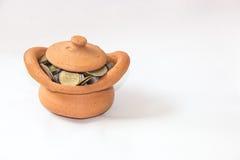 Ataúd de la arcilla por completo de las monedas para el concepto de la economía imagenes de archivo