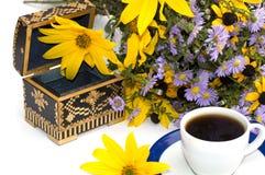 Ataúd, taza de café, ramo de flores salvajes y flor amarilla Foto de archivo libre de regalías