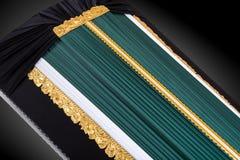 Ata?d verde oscuro cerrado cubierto con el pa?o elegante en fondo gris primer del ata?d imagen de archivo