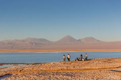 Atacama, Chile - Oct 9th 2017 - Group of tourists appreciating the sunset at the Atacama Desert Salt Flat, blue water, volcano in stock photos