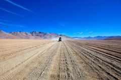 Atacama Desert Bolivia. Secluded road with Jeep in Atacama desert, Bolivia royalty free stock photos