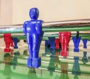 Atacante de uma tabela vermelha e azul do futebol em uma sala de jogo imagens de stock