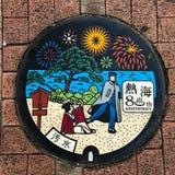 Atami, Japon : chapeau d'égout/couverture de trou d'homme/trappe, moyens Atami de langue japonaise et eaux d'égout images libres de droits