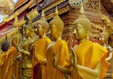 Atand de statues de Bouddha d'or dans une rangée Photographie stock libre de droits