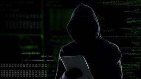 Ataque cibernético con el pirata informático encapuchado irreconocible que usa la tableta, ciberdelincuencia almacen de video