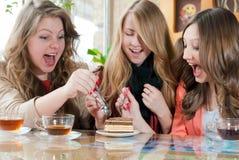 Ataque contra la torta y los amigos de muchacha felices emocionados Fotos de archivo