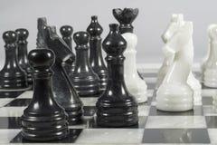 Ataque de los pedazos negros en el curso de un partido del ajedrez Tablero de ajedrez de mármol Imágenes de archivo libres de regalías