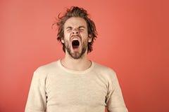 Ataque de nervios Hombre soñoliento con la barba en fondo rojo foto de archivo