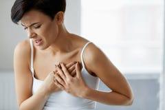 Ataque del corazón Dolor hermoso de la sensación de la mujer en atención sanitaria del pecho imagen de archivo libre de regalías