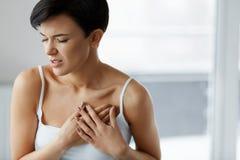 Ataque del corazón Dolor hermoso de la sensación de la mujer en atención sanitaria del pecho imagen de archivo