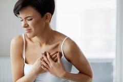 Ataque del corazón Dolor hermoso de la sensación de la mujer en atención sanitaria del pecho imagenes de archivo