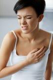 Ataque del corazón Dolor hermoso de la sensación de la mujer en atención sanitaria del pecho fotografía de archivo libre de regalías