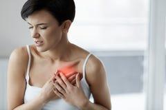 Ataque del corazón Dolor hermoso de la sensación de la mujer en atención sanitaria del pecho foto de archivo libre de regalías