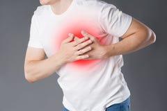 Ataque del corazón, hombre con dolor de pecho en fondo gris fotos de archivo