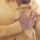 Ataque del corazón, mano del uso que ase un pecho Imágenes de archivo libres de regalías