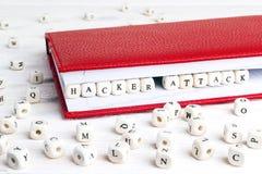 Ataque del pirata informático de la frase escrito en bloques de madera en cuaderno rojo encendido Fotografía de archivo