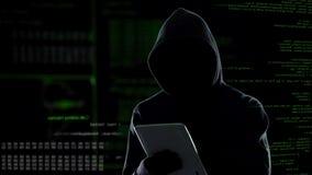 Ataque do Cyber com o hacker encapuçado irreconhecível que usa o tablet pc, cibercrime video estoque