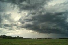Ataque o ciclone sobre campos, florestas e montes do verão imagem de stock