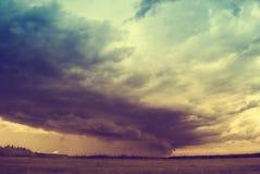 Ataque o ciclone sobre campos, montes e florestas do verão imagens de stock royalty free